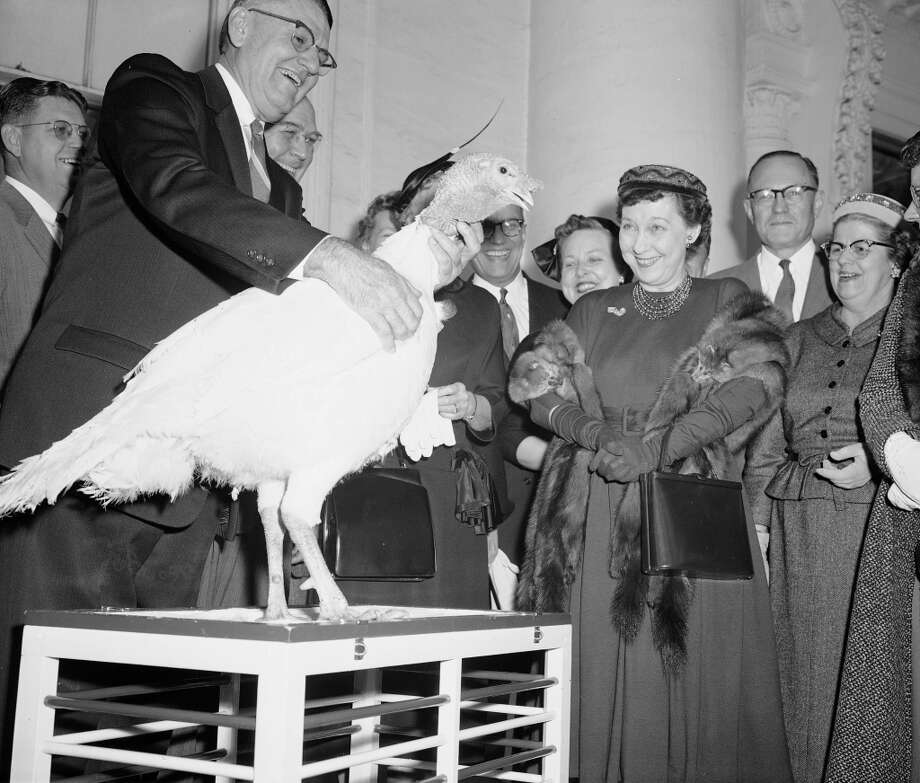 First lady Mamie Eisenhower is amused by the gobbling of a 40-pound tom turkey presented to her at the White House, Nov. 14, 1957, fo rthe Eisenhower's Thanksgiving dinner.  Mrs. Eisenhower accepted the Illinois-raised turkey just before going to a luncheon party celebrating her 61st birthday.  Others are unidentified.  (Charles Gorry/AP) Photo: Charles Gorry, ASSOCIATED PRESS / AP1957