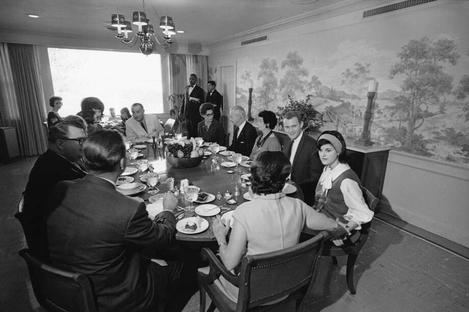 President Lyndon Johnson, seated at head of table, as family and friends gather for Thanksgiving Day dinner at the LBJ Ranch in Stonewall, Texas, Nov. 25, 1965. Clockwise from the President are: Mrs. T.J. Taylor III; J.C. Kellam;  Lela Martin, cousin of the president; Pat Nugent, Luci?s boyfriend; Luci Baines, and Lady Bird Johnson. Lynda Bird is seated to the president?s right and Press Secretary Bill Moyers. Man with glasses is Earl Deathe.  (Charles Tasnadi/AP) Photo: Charles Tasnadi, ASSOCIATED PRESS / AP1965