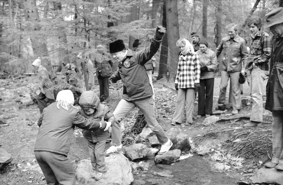 Amy Carter reaches out to help nephew Jason as President Jimmy Carter jumps from rock to rock while crossing a creek during an outing at Cunningham Falls State Park, Maryland, Nov. 24, 1978. The park is near the presidential retreat Camp David where the first family spent Thanksgiving.  (Barry Thumma/AP) Photo: Barry Thumma, ASSOCIATED PRESS / AP1978