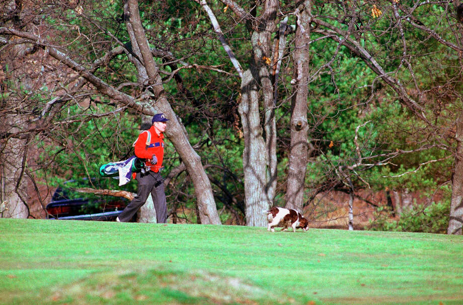 U.S. President George H. Bush carries his golf clubs as he makes his way down a fairway with one of the Bush family dogs at the Cape Arundel Golf Course in Kennebunkport, Maine, Saturday, Nov. 28, 1992. Bush is spending long Thanksgiving Day weekend at the family home at Walker's Point.  (Jim Cole/AP) Photo: Jim Cole, ASSOCIATED PRESS / AP1992