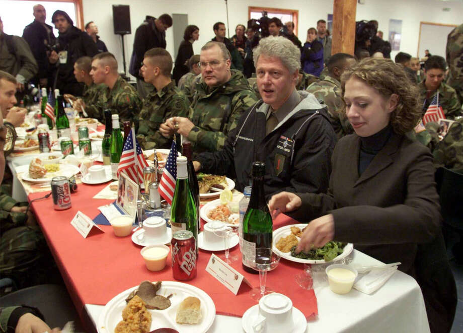 President Bill Clinton and his daughter Chelsea, right, join Camp Bondsteel's commanding officer, Task Force Falcon Commander Brig. Gen. Craig A. Peterson, third right, for a pre-Thanksgiving dinner at Camp Bondsteel, Kosovo, Yugoslavia, Tuesday, Nov. 23, 1999. Kosovo is the final stop on Clinton's trip, which began in Turkey. A major theme has been finding a long-term solution to the political, economic and social instabilities in the Balkans.   (Greg Gibson/AP) Photo: GREG GIBSON, ASSOCIATED PRESS / AP1999