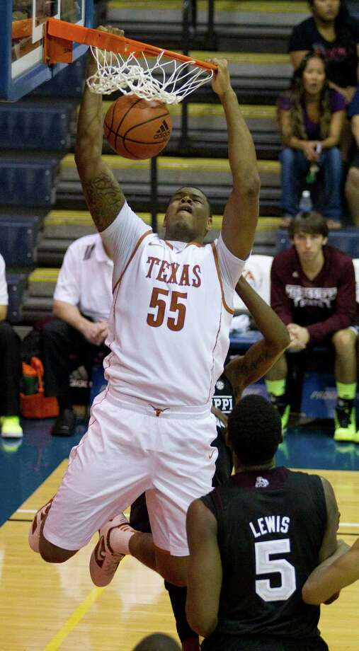 Texas center Cameron Ridley (55) dunks the basketball as Mississippi State center Wendell Lewis (5) looks on in the first half of an NCAA college basketball game in the Maui Invitational Wednesday, Nov. 21, 2012, in Lahaina, Hawaii. (AP Photo/Eugene Tanner) Photo: Eugene Tanner, Associated Press / FR168001 AP