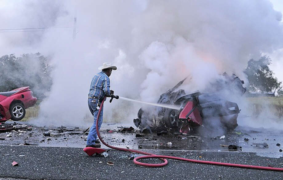 Two people were killed in a two-vehicle crash in Atascosa County on Wednesday morning. A Department of Public Safety spokesman said the head-on collision happened about 7 a.m. on FM 476 near Rogers Road, just outside of Poteet. Nemencio Tijerina with the Poteet Volunteer Fire Department douses the flames on one of the vehicles. Investigators said a man driving a 1997 Pontiac was driving west on FM 476,  when he veered into oncoming traffic and crashed head-on into a 1997 Honda. The two people in the Honda died in the crash and the man in the Pontiac was transported by a medical helicopter to University Hospital. Photo: Xavier Garcia, For The Express-News