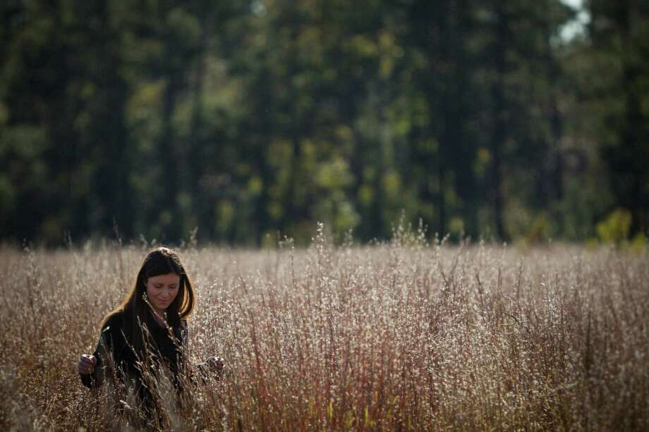Sarah Mitchell, executive director of the Cook's Branch Conservancy, right, walks through a field of Little Bluestem grass while at the 5,650 acres in Montgomery County north of Houston, Wednesday, Nov. 14, 2012, in Montgomery.  Operated as a program of the Cynthia and George Mitchell Foundation, Cook's Branch Conservancy offers a rare glimpse into what nearly a century of regeneration looks like in the Pineywoods region of East Texas. Photo: Michael Paulsen, Houston Chronicle / © 2012 Houston Chronicle