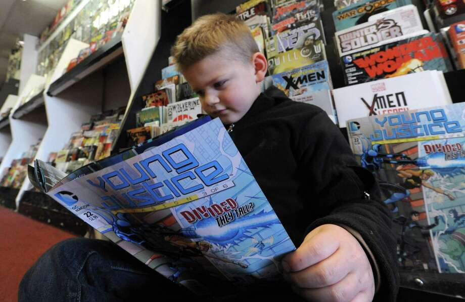 Five-year-old Jason DeVito of Amsterdam looks over a comic book at Earthworld Comics in Albany, NY Wednesday Nov. 21, 2012. (Michael P. Farrell/Times Union) Photo: Michael P. Farrell