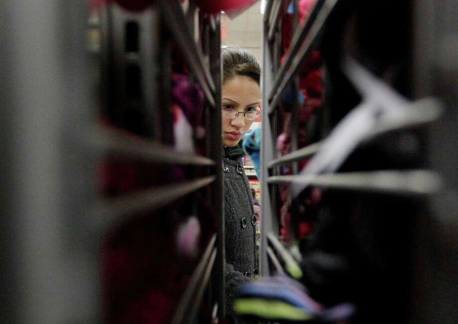 FILE - In this Friday, Nov. 25, 2012, file  photo, a customer shops at a K-Mart in Chicago. If the economic downturn has taught retailers anything, it's that a 50 percent off sale isn't enough to lure finicky American shoppers into stores these days, so this holiday season, shoppers will find that retailers are doing all kinds of things to make it easier for them to part with their money. (AP Photo/Nam Y. Huh, File) Photo: Nam Y. Huh