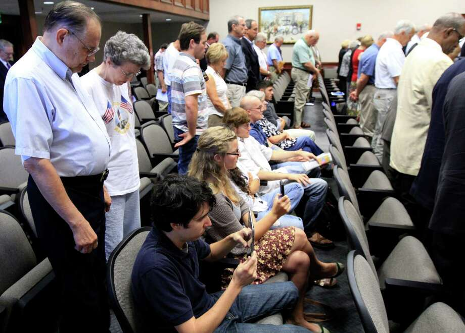 Protesters remain seated during a Hamilton County Commission meeting in Chattanooga, Tenn., earlier this year. Such prayers at public meetings are increasingly under attack. Photo: Dan Henry, MBO / Dan Henry/Chattanooga Times Free
