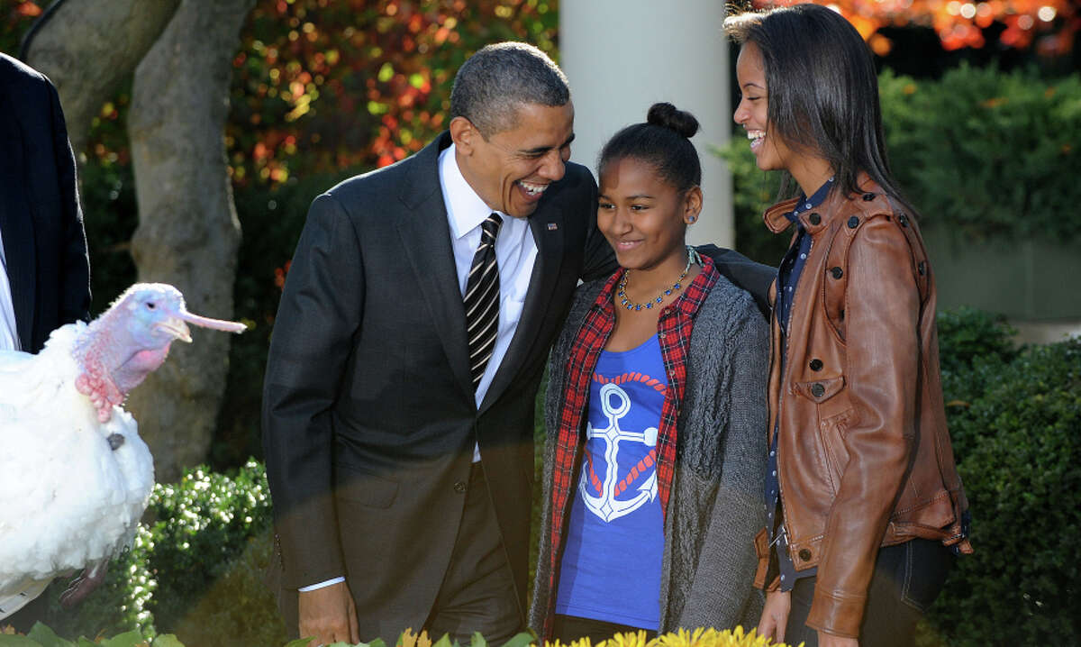President Barack Obama shares a laugh with daughters Sasha, center, and Malia after pardoning two turkeys.