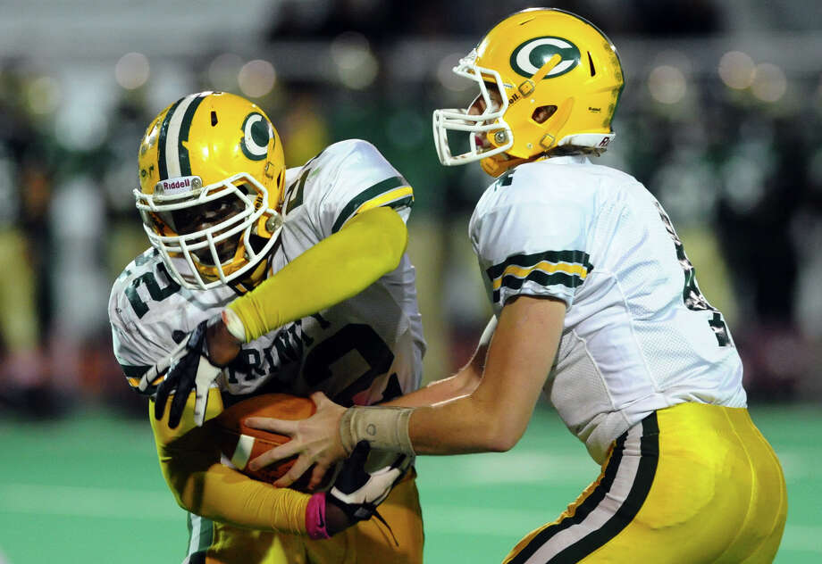 Trinity Catholic QB Danny O'Leary hands off the ball to #22 Shaquan Howsie, during boys football action against Bassick in Bridgeport, Conn. on Friday October 26, 2012. Photo: Christian Abraham / Connecticut Post