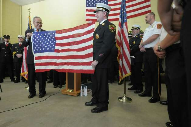 U.S. Senator Charles Schumer, left, and Clinton Heights fire Department assistant chief Seth Tracy hold a flag that the senator presented to the fire department at the Clinton Heights  fire house on Wednesday, Nov. 21, 2012 in East Greenbush, NY.  Senator Schumer came to the fire house on Wednesday to thank the members of the East Greenbush, Melrose, Poestenkill and Clinton Heights fire departments for their service in helping to rescue people in the parts of New York devastated by the storm Sandy.  Senator Schumer presented each fire house with a flag that had been flown over the Capital in Washington.   Firefighters from the four stations, that were type II swift-water rescue certified along with a medic from the Nassau Fire Department rescued 16 adults, seven children and three animals.   (Paul Buckowski / Times Union) Photo: Paul Buckowski  / 00020216A