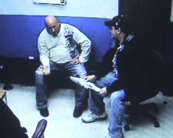 Frame grab from stationhouse video footage of Albany police officer Brian Lutz?s, left, arrest in Menands. Christian Mesley, the former Albany police union president, is pictured right.