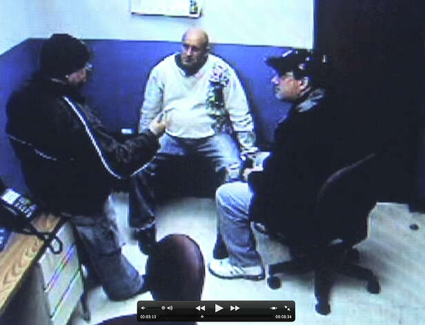 Frame grab from stationhouse video footage of Albany police officer Brian Lutz?s, center, arrest in Menands. Albany police officer, Charles Batchelor, left, and former Albany police union president, Christian Mesley, right, are shown counseling officer Lutz. (Times Union)