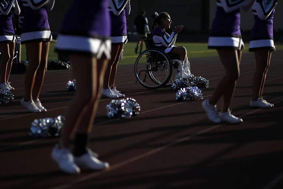 Angel Gonzalez-Prado, whose legs have been paralyzed by spina bifida, cheers from her wheelchair with her squad at Sequoia High School in Redwood City. Photo: Beck Diefenbach, Special To The Chronicle
