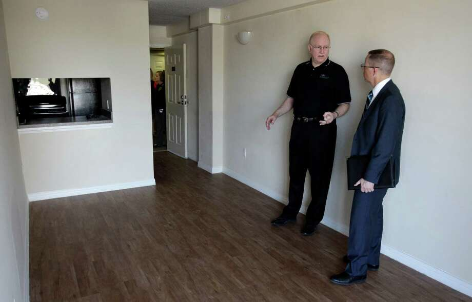 Johnnie Johnson, property manager at 2100 Memorial, on Wednesday shows Neal J. Radkleff, director of the city's Housing and Community Development Department, an example of the type of housing available under the new program. Photo: Melissa Phillip, Staff / © 2012 Houston Chronicle