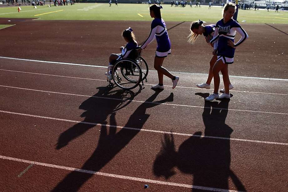 Sequoia High School junior varsity cheerleader Angel Gonzalez-Prado (in wheelchair) prepares with her teammates to greet the cheerleaders from the opposing team during the junior varsity football game on Friday, September 28, 2012 in Redwood, Calif. Photo: Beck Diefenbach, Special To The Chronicle