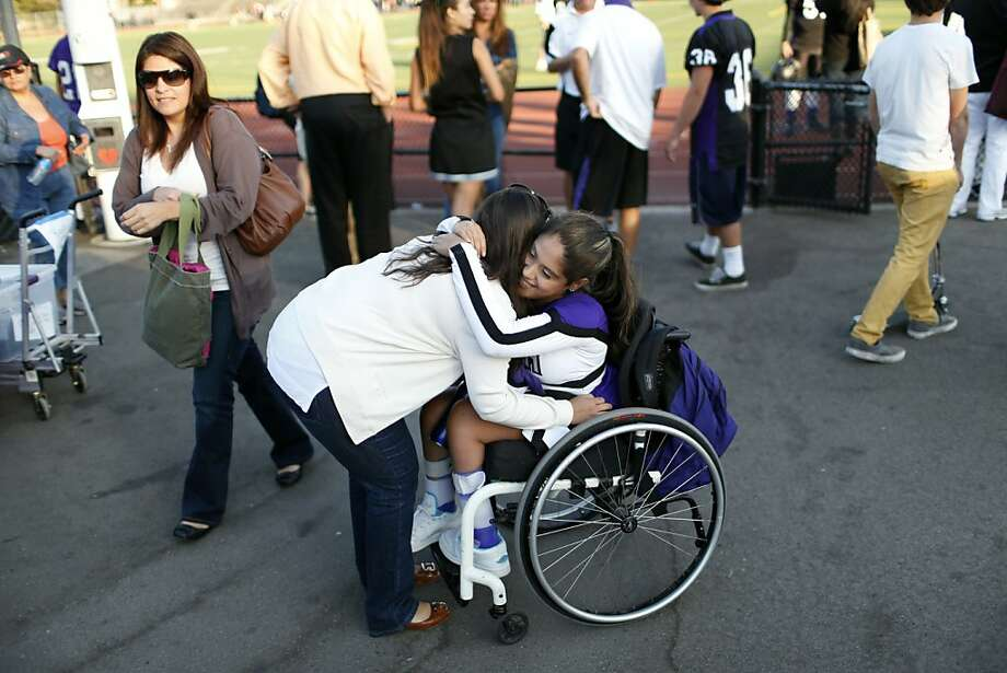 Sequoia High School junior varsity cheerleader Angel Gonzalez-Prado (in wheelchair) in embraced by her mother Cynthia Prado following the junior varsity football game on Friday, September 28, 2012 in Redwood, Calif. Photo: Beck Diefenbach, Special To The Chronicle
