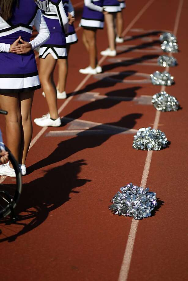 The shadows of the Sequoia High School junior varsity cheerleaders are cast onto the track during the junior varsity football game on Friday, September 28, 2012 in Redwood, Calif. Photo: Beck Diefenbach, Special To The Chronicle