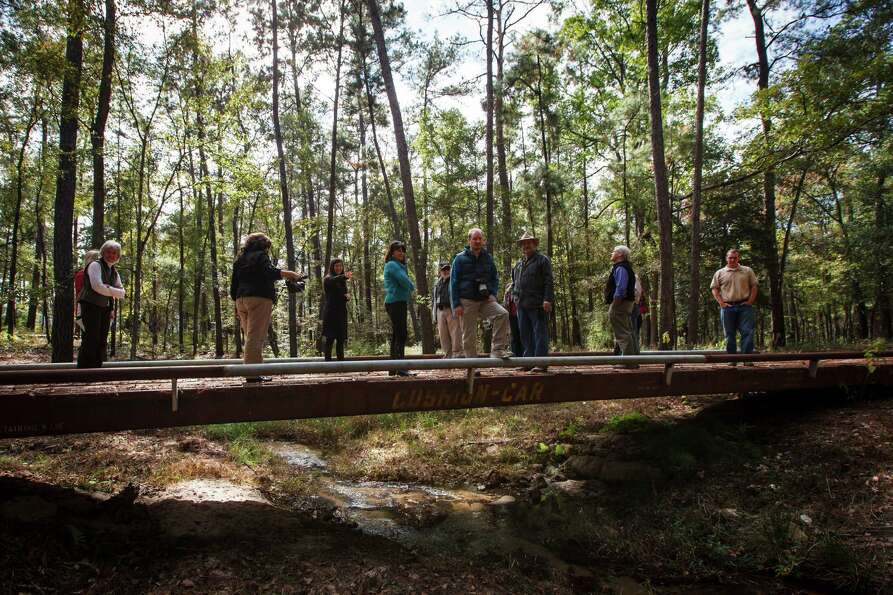 Visitors stand on a bridge spanning across Cook's Branch stream while at the 5,650 acres of Cook's B