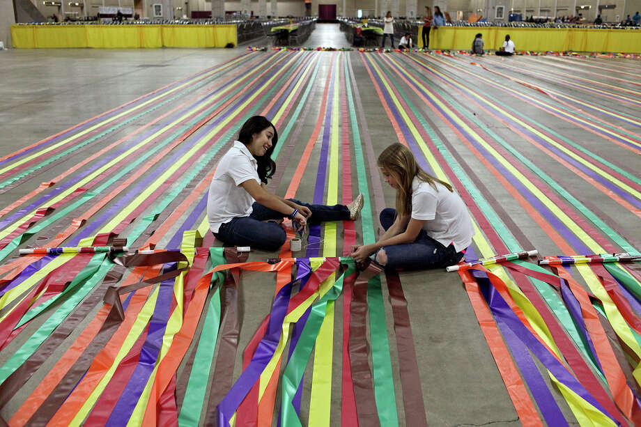 Camryn Galvan, 13, left, and Lexi Bracken, 13, help prepare decorations for The Raul Jimenez Thanksgiving Dinner at the Henry B. Gonzalez Convention Center in San Antonio on Wednesday, Nov. 21, 2012. The girls are with Girl Scout Troop 600 from St. Luke Catholic School and volunteering for the event is part of their monthly service project. Photo: Lisa Krantz, San Antonio Express-News / © 2012 San Antonio Express-News