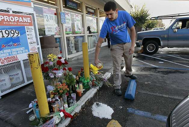 Manuel Chavez pours beer on the spot where Rory Park-Pettiford was killed outside a 7-Eleven store when assailants tried to steal his car during a violent spree that included four armed robberies and a shootout. Photo: Michael Macor, The Chronicle