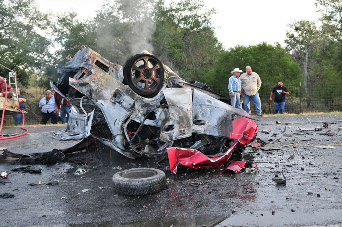 Officials work the scene of a fatal accident near Poteet Wednesday morning. DPS Trooper Jason Reyes said a Pontiac heading east on FM 476 near Texas 16 veered into oncoming traffic about 7 a.m., slamming into a Honda and killing the two occupants.