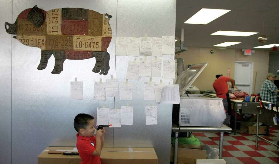 Gabriel Martinez, grandson of Michael Cruz, plays with his toy gun at Pete's Fine Meats where 10 family members work side-by-side at the butcher shop Wednesday, Nov. 21, 2012, in Houston. The family business that started in 1960 closed in January after a fire.  The business just reopened last week, in time to sell turkeys and other meat for Thanksgiving. Photo: Johnny Hanson, Houston Chronicle / © 2012  Houston Chronicle