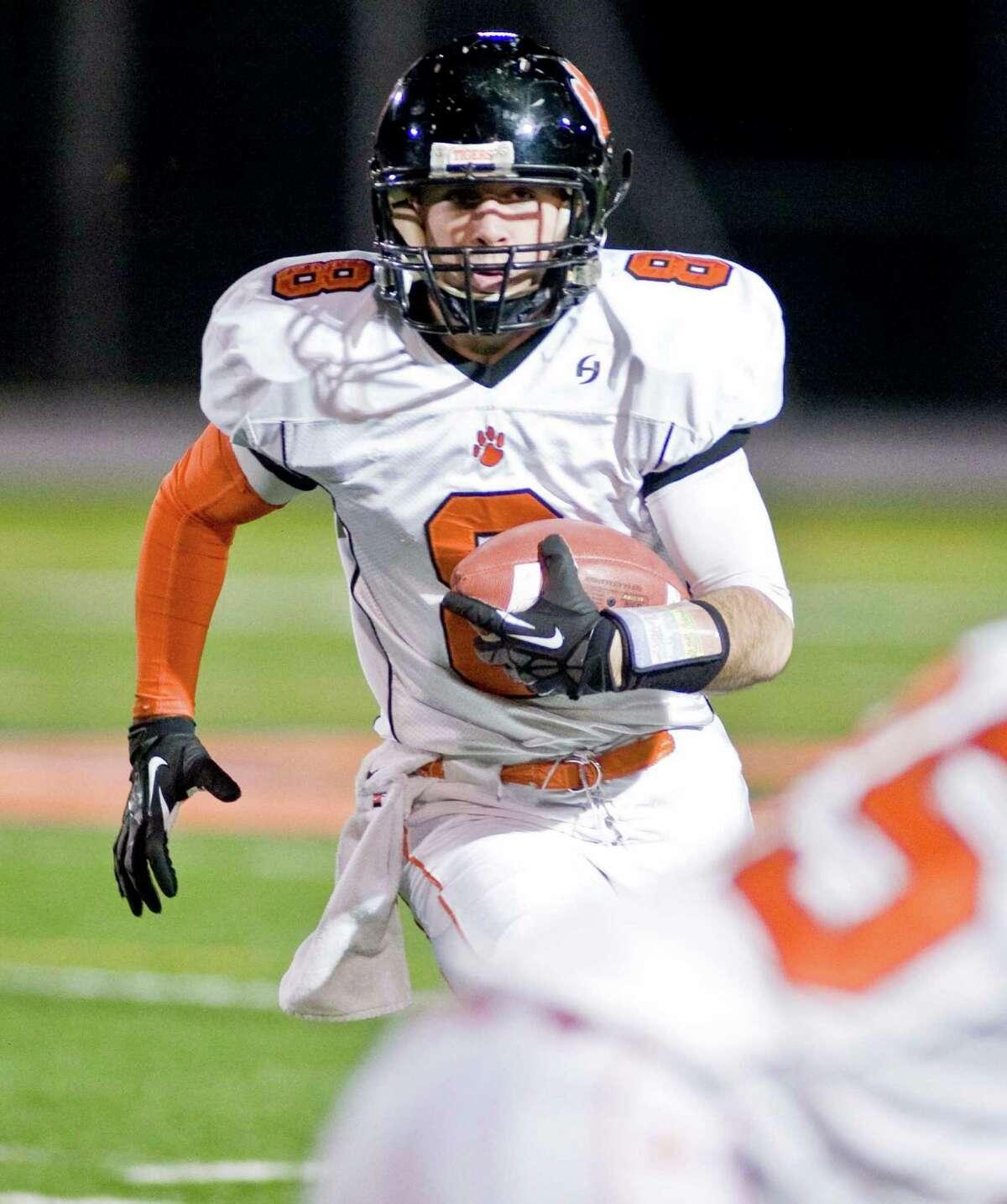 Ridgefield High School quarterback Connor Rowe looks for a lane through the Danbury High School defense in a game at Danbury. Wednesday, Nov. 21, 2012