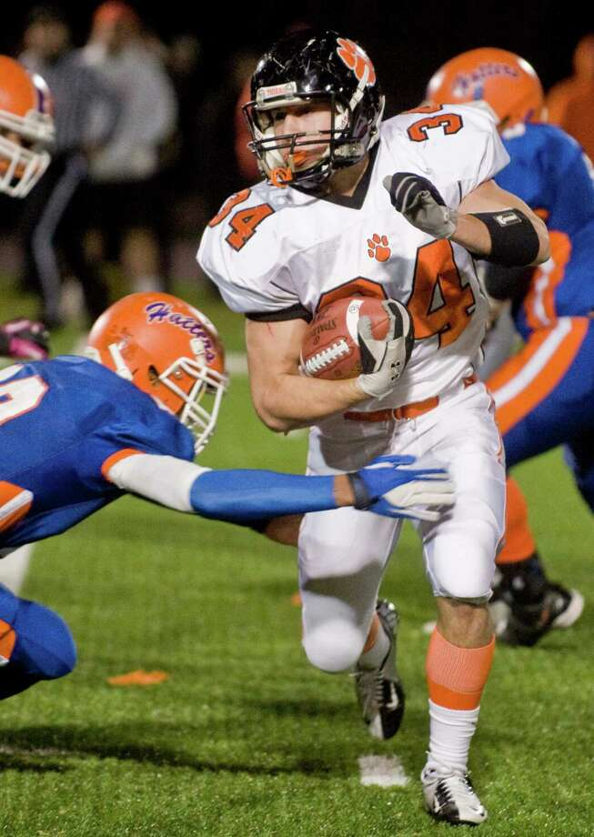 Ridgefield High School's Will Bonaparte slips through a tackle during a game against Danbury High School, played at Danbury. Wednesday, Nov. 21, 2012 Photo: Scott Mullin / The News-Times Freelance