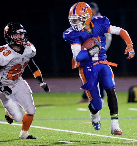 Ridgefield High School's Mickey Hicks chases Danbury High School wide receiver Corey Chaffee in a game at Danbury. Wednesday, Nov. 21, 2012 Photo: Scott Mullin / The News-Times Freelance