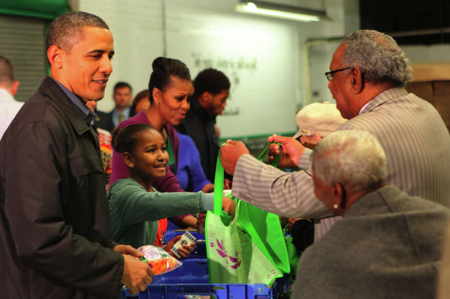 U.S. President Barack Obama (L), First Lady Michelle Obama (C) and Sasha (2nd-L) and Malia Obama fill bags with produce at the Capital Area Food Bank on November 23, 2011 in Washington, DC. Earlier in the day Preident Barack Obama, during an annual Thanksgiving tradition, pardoned two turkeys.  (Dennis Brack-Pool/Getty) Photo: Pool, Getty Images / 2011 Getty Images