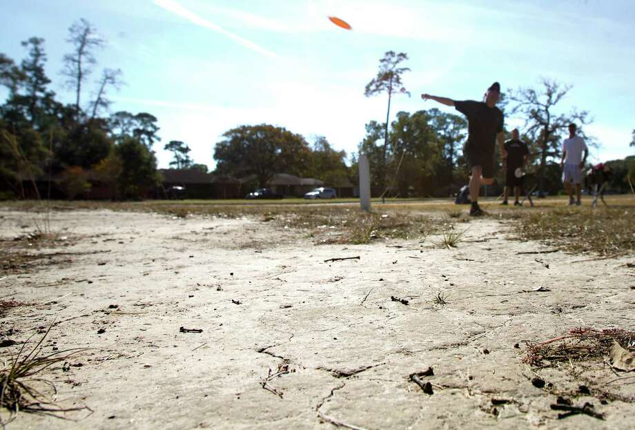 "The ground at TC Jester Park is bald where Gregg Brattin plays a game of disc golf on Wednesday. ""I don't remember the last time it's rained here,"" he said. Photo: Cody Duty, Staff / © 2012 Houston Chronicle"