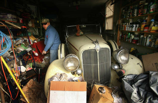 Far Rockaway homeowner Kurt Schneck stands by his rare 1934 Chrysler convertible, damaged by Hurricane Sandy flooding, on Sunday, November 18, 2012. Photo: Brian A. Pounds / Connecticut Post