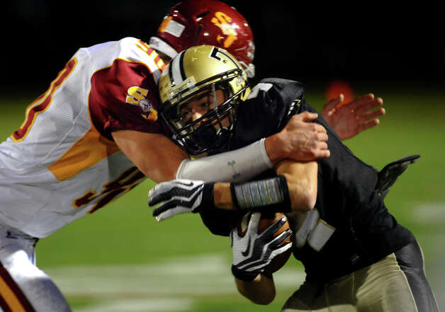 Trumbull's #4 Marc Cesare is tackled by St. Joseph's #90 Ryan Moran, during boys football action in Trumbull, Conn. on Wednesday November 21, 2012. Photo: Christian Abraham / Connecticut Post