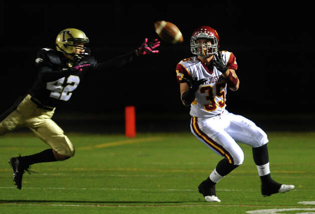 St. Joseph's #35 Mark Hirschbeck catches a pass as Trumbull's #42 Nick DeRosa tries to block, during boys football action in Trumbull, Conn. on Wednesday November 21, 2012. Hirschbeck took this ball to the endzone for a touchdown. Photo: Christian Abraham / Connecticut Post
