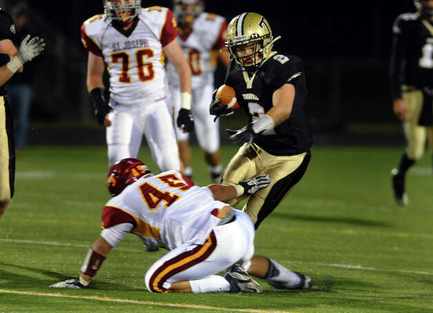 Trumbull's #2 Ryan Pearson tries to evade St. Joseph's #45 Mike Pulaski, during boys football action in Trumbull, Conn. on Wednesday November 21, 2012. Photo: Christian Abraham / Connecticut Post