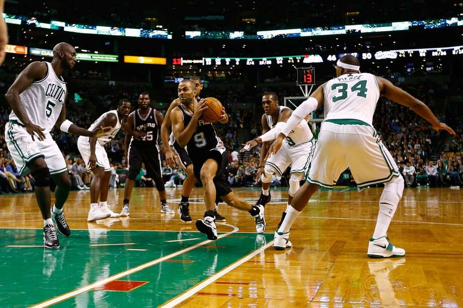 Tony Parker (9) of the Spurs drives to the basket past in between Kevin Garnett (5) and Paul Pierce (34) of the Celtics on Nov. 21, 2012 at TD Garden in Boston. (Jared Wickerham / Getty Images)