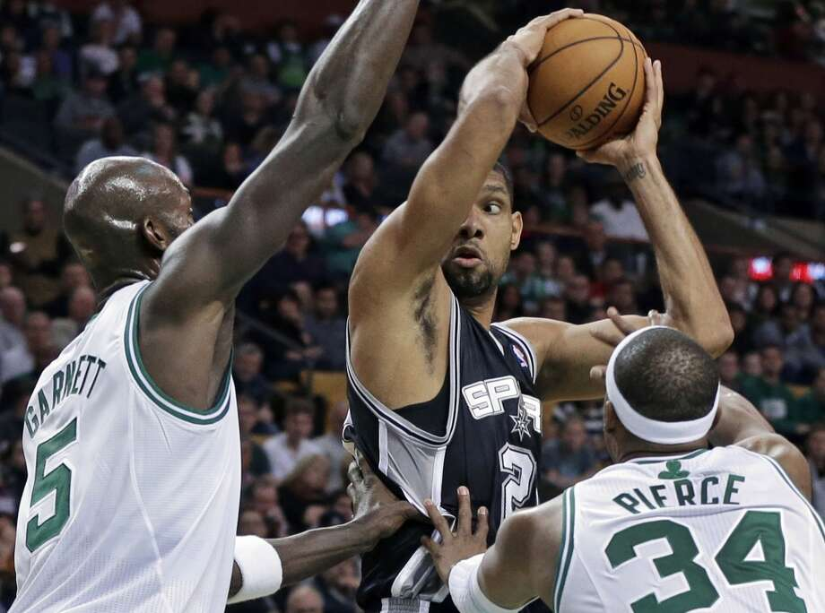 Spurs forward Tim Duncan, center, looks to pass the ball against the defense of Boston Celtics forward Kevin Garnett (5) and forward Paul Pierce (34) during the first half of an NBA basketball game in Boston, Wednesday, Nov. 21, 2012.  (Elise Amendola / Associated Press)