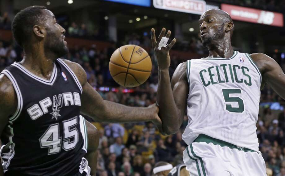 A loose ball slips between Celtics forward Kevin Garnett (5) and Spurs center DeJuan Blair (45) during the first half of an NBA basketball game in Boston, Wednesday, Nov. 21, 2012. (Elise Amendola / Associated Press)