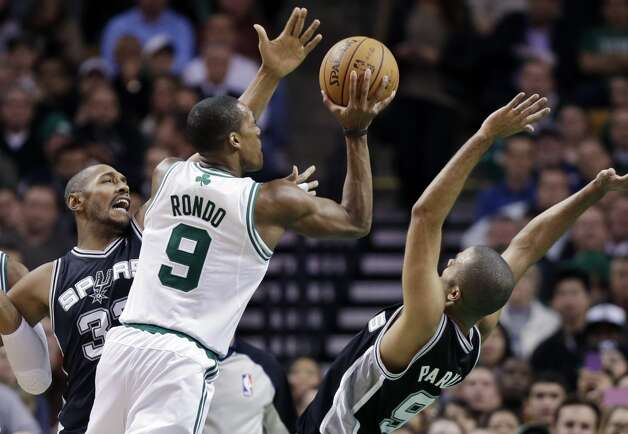 Celtics point guard Rajon Rondo (9) shoots between Spurs center Boris Diaw (left) and guard Tony Parker (right)  during the first half in Boston, Wednesday, Nov. 21, 2012. (Elise Amendola / Associated Press)