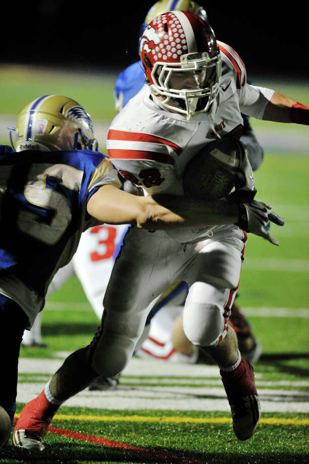 Masuk's Thomas Milone runs the ball in for a touchdown while under pressure from Newtown's Julian Dunn during their game at Newtown High School on Wednesday, Nov. 21, 2012. Newtown beat the undefeated Masuk, 21-14. Photo: Jason Rearick / The News-Times