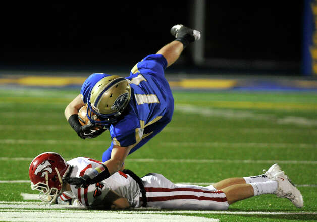 Newtown's Cooper Gold is tripped up by Masuk's Kyle Fonteau during their game at Newtown High School on Wednesday, Nov. 21, 2012. Newtown beat the undefeated Masuk, 21-14. Photo: Jason Rearick / The News-Times