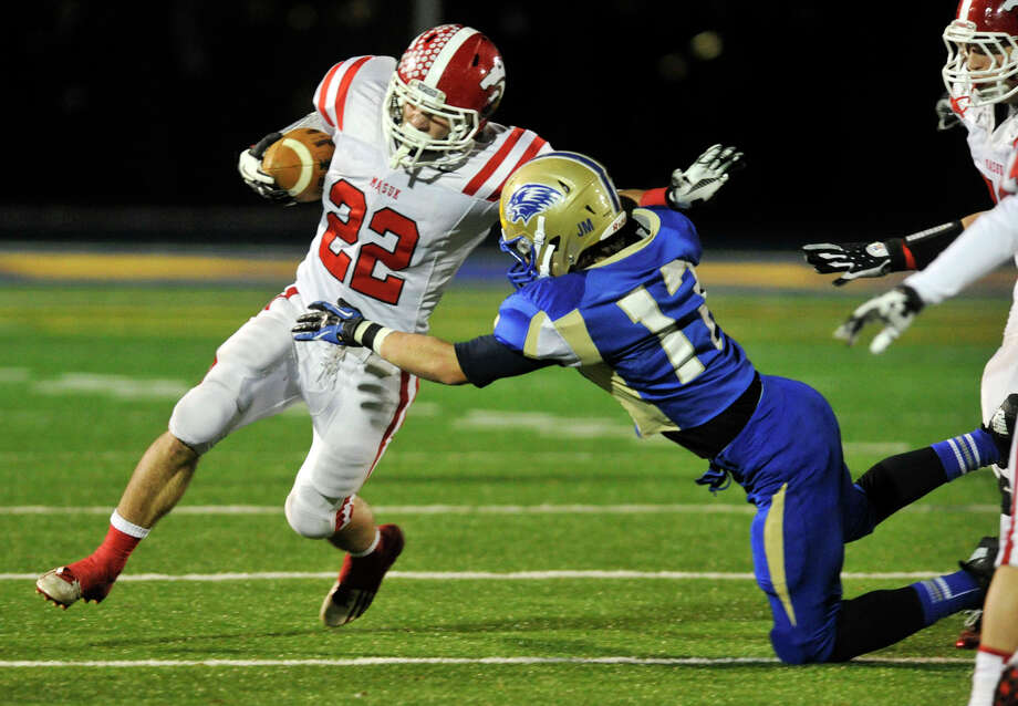 Masuk's Thomas Milone meets resistance from Newtown's Wyatt Depuy during their game at Newtown High School on Wednesday, Nov. 21, 2012. Newtown beat the undefeated Masuk, 21-14. Photo: Jason Rearick / The News-Times