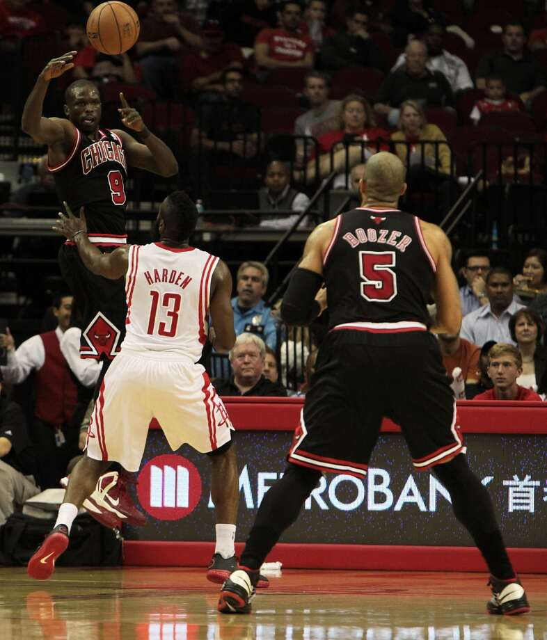 Luol Deng left, passes the ball over the Rockets James Harden center, to teammate Carlos Boozer right. (James Nielsen / Houston Chronicle)