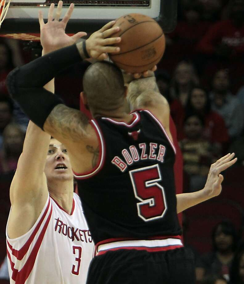Omer Asik left, defends the Bulls Carlos Boozer.( James Nielsen / Chronicle ) (James Nielsen / Houston Chronicle)