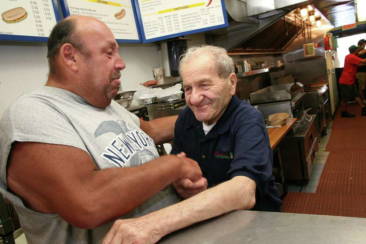 """Garden Catering employee Frank """"Hotsy"""" Bertino greets regular customer Tom Wilcox July 8, 2011. After 60 years in the food service business in Greenwich, Bertino died of natural causes Tuesday night, Nov. 20, 2012, at Greenwich Hospital, according to his family. The Cos Cob resident was 91."""