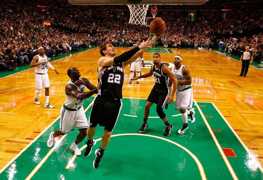 Tiago Splitter #22 of the San Antonio Spurs drives to the basket for a layup in front of Brandon Bass #30 of the Boston Celtics on Nov. 21, 2012 at TD Garden in Boston. (Jared Wickerham / Getty Images)
