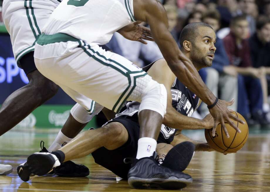 San Antonio Spurs point guard Tony Parker (9) looks to pass the ball from the floor against the defense of Boston Celtics point guard Rajon Rondo and forward Brandon Bass, behind, during the first half of an NBA basketball game in Boston, Wednesday, Nov. 21, 2012. The Spurs won 112-100.  (Elise Amendola / Associated Press)