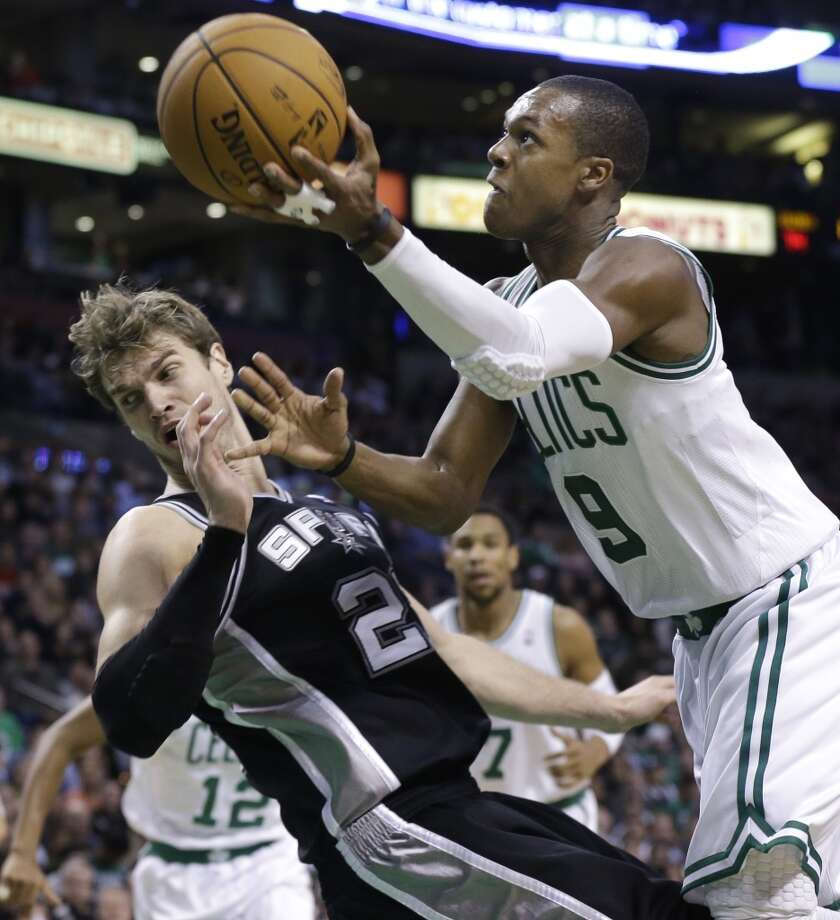 Boston Celtics point guard Rajon Rondo (9) drives to the hoop against San Antonio Spurs power forward Tiago Splitter, left, during the second half of an NBA basketball game in Boston, Wednesday, Nov. 21, 2012. The Spurs won 112-100.  (Elise Amendola / Associated Press)
