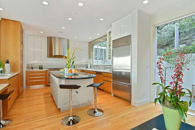 The stainless steel island kitchen features hardwood flooring, decorative and recessed lighting, and a sliding-glass door leading to the rear patio and garden. Photo: REC_9_Clarendon_Ave_18