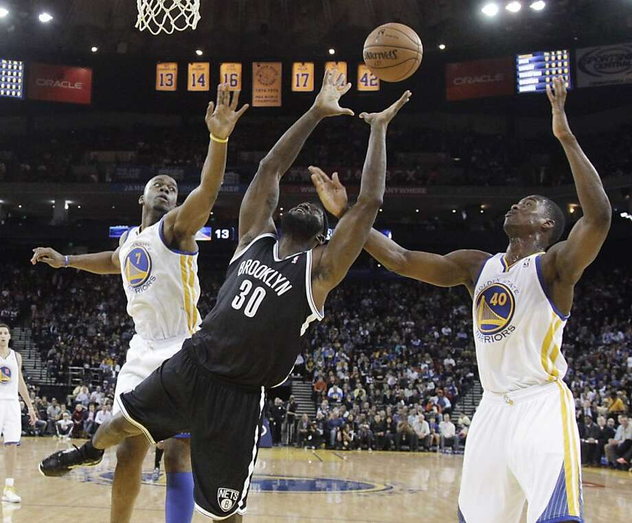 Brooklyn Nets' Reggie Evans (30) grabs a rebound between Golden State Warriors' Carl Landry (7) and Harrison Barnes (40) during the first half of an NBA basketball game in Oakland, Calif., Wednesday, Nov. 21, 2012. (AP Photo/Marcio Jose Sanchez) Photo: Marcio Jose Sanchez, Associated Press